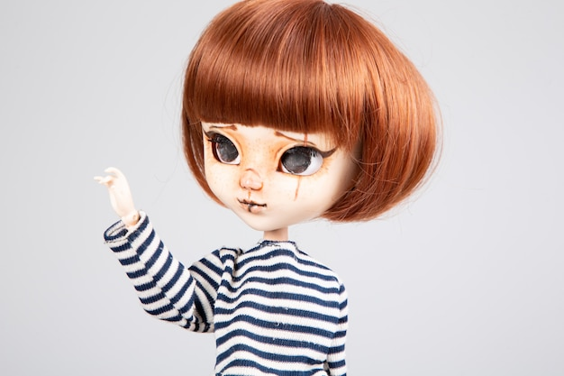 Bonita muñeca pelirroja con la mano levantada