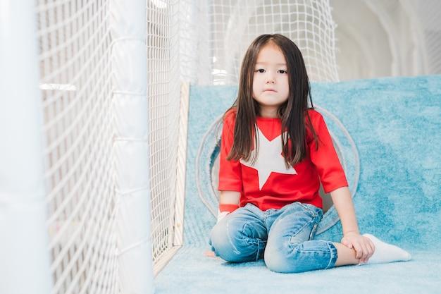 Bonita niña asiática con el pelo largo con traje de super chica mirándote en el área de juego