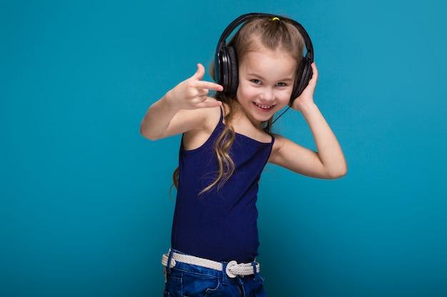 Bonita niña de camisa y auriculares con pelo brunet.