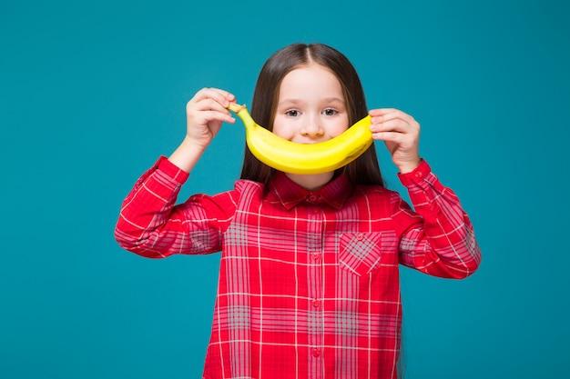 Bonita, niña en camisa a cuadros con brunet, asimiento de frutas.