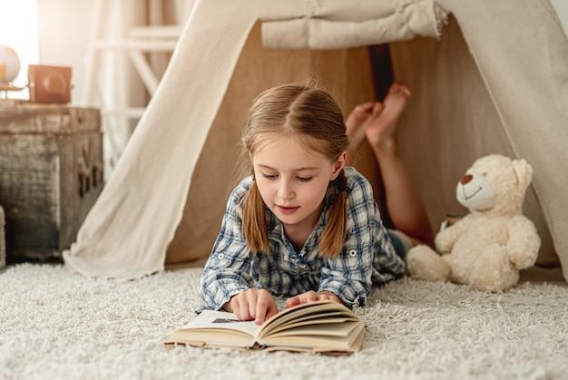 Bonita niña con oso y libro de papel sentado en el suelo de la habitación decorado con wigwam, cofre y linterna retro