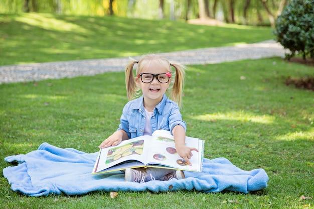 Una bonita niña rubia con cabello rubio y gafas de lectura leyendo un libro en un parque