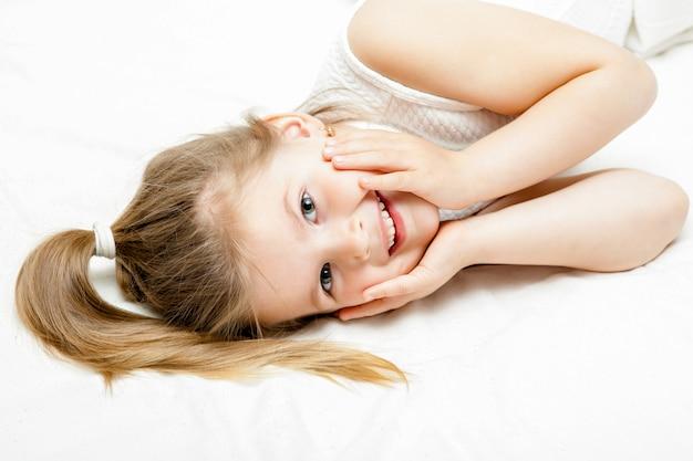 Bonita niña rubia vestido blanco de verano tirado en el piso y sonriendo a la cámara en blanco
