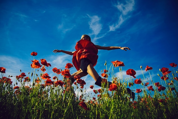 Bonita niña saltando en campo de flores de semillas de amapola