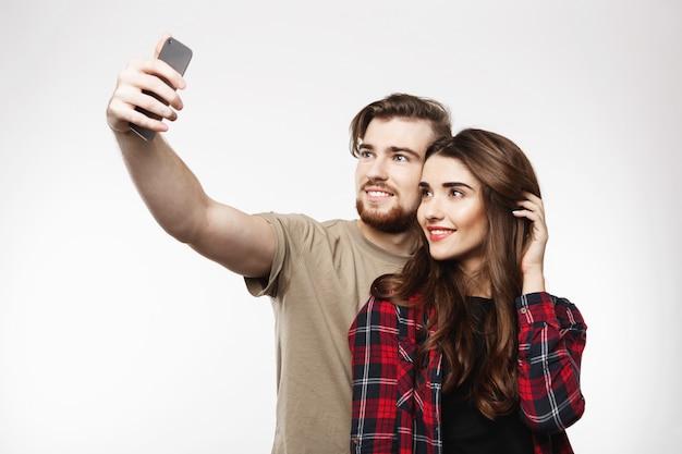 Bonita pareja alegre tomando selfie en teléfono, mirando feliz.