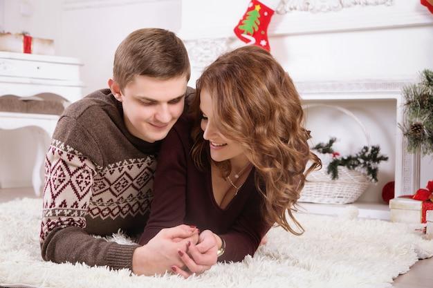 Bonita pareja de amor en la alfombra. mujer y hombre celebrando la navidad