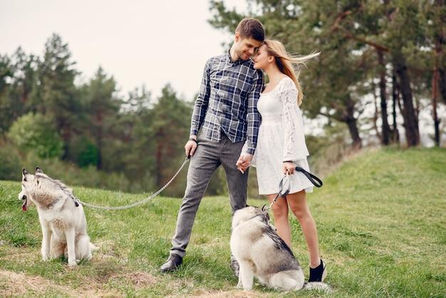 Bonita pareja en un bosque de verano con perros.