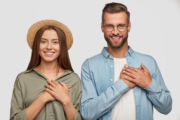 Bonita pareja de buen corazón posando contra la pared blanca