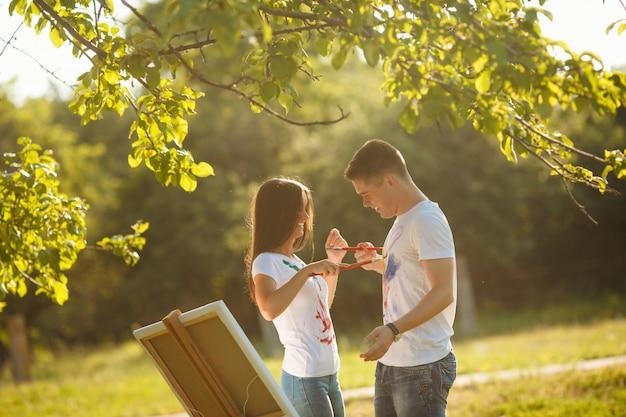 Bonita pareja divirtiéndose al aire libre al aire libre. hombre joven y mujer que dibujan por las pinturas coloridas en las camisetas del `s del otro con los cepillos cerca del caballete en la naturaleza.