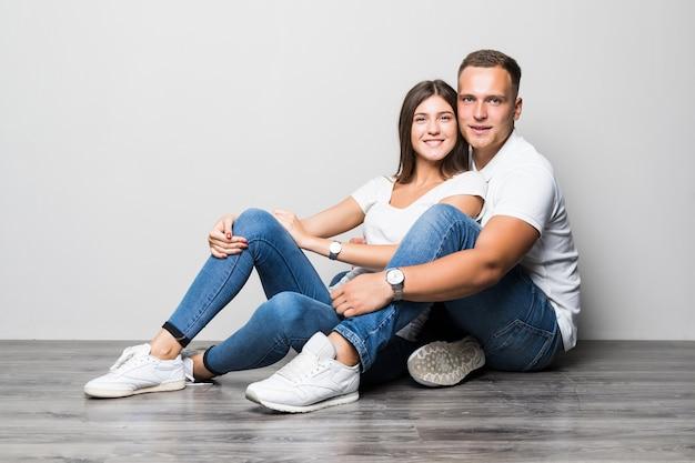 Bonita pareja elegante abrazándose juntos mientras está sentado en el suelo aislado sobre fondo blanco.