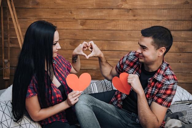 Bonita pareja de enamorados mirándose y sosteniendo corazones de papel rojo sentado en la cama