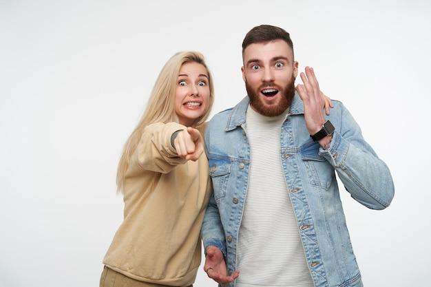 Bonita pareja joven asombrada levantando emocionalmente sus manos mientras mira sorprendido con los ojos abiertos, de pie en blanco