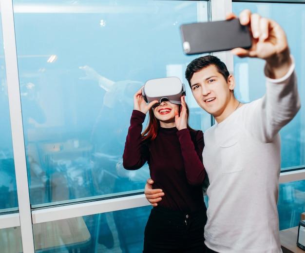 Bonita pareja joven entusiasta tomando selfie