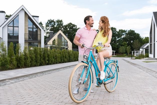Bonita pareja positiva en bicicleta mientras tiene una cita