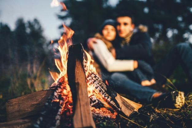 Bonita pareja relajante cerca de la hoguera en el bosque en el momento de la noche