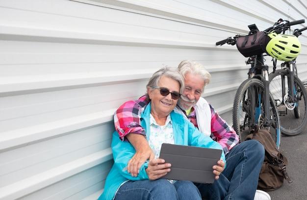 Una bonita pareja senior sentada contra una pared de metal blanco cerca de sus bicicletas eléctricas. mirando juntos la misma tableta