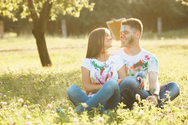 Bonita pareja sentada en el césped al aire libre. hermosa chica y hombre guapo mirando el uno al otro y sonriendo al aire libre con camisetas coloreadas