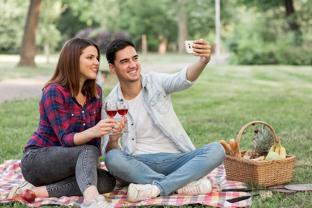 Bonita pareja tomando un selfie mientras sostiene copas de vino