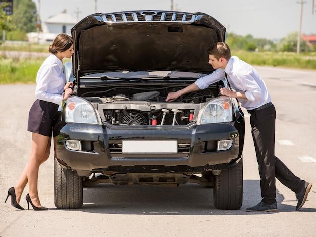 Bonita pareja está tratando de reparar su automóvil usando el manual.