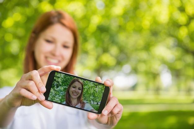 Bonita pelirroja tomando un selfie en su teléfono en el parque