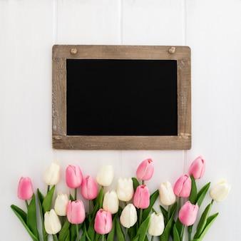 Bonita pizarra con ramo de tulipanes.