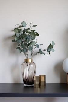Bonita planta artificial en florero de vidrio con borde de acero inoxidable dorado y florero de espejo dorado y ajuste de lámpara en la mesa de madera negra vacía.