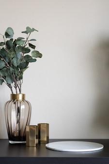 Bonita planta artificial en florero de vidrio con borde de oro inoxidable y florero de espejo dorado en la parte superior de madera