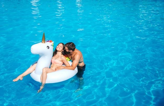 Bonita y positiva imagen de hombre y mujer nadando en la piscina. niña sentada sobre un colchón de aire. ella se está riendo. guy se para junto a ella y se inclina hacia ella. tienen un poco de descanso.