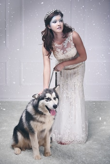 Bonita reina de hielo con perro entre la nieve cayendo