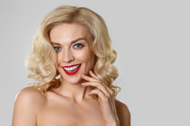 Bonita rubia con cabello ondulado, maquillaje de ojos de gato y labios rojos.