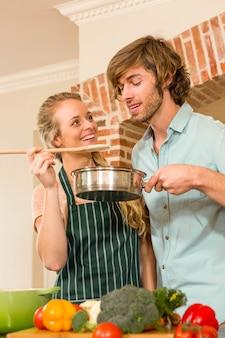 Bonita rubia haciendo que su novio pruebe la preparación en la cocina