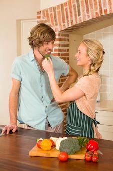 Bonita rubia haciendo que su novio pruebe una verdura en la cocina