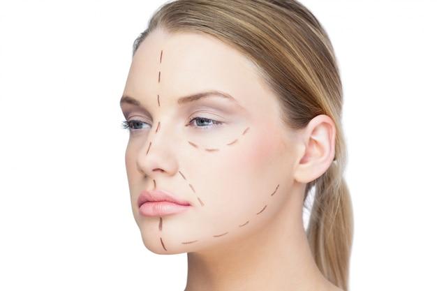 Bonita rubia con líneas punteadas en la cara.
