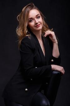 Bonita rubia con maquillaje. una chica atractiva con cabello largo y hermoso sentada en una silla.