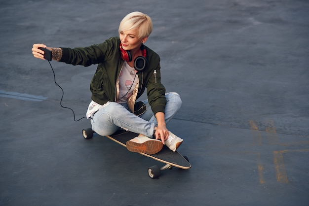 Bonita rubia mujer con auriculares, haciendo auto foto en el teléfono mientras está sentado en el longboard al atardecer.