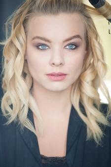 Bonita rubia con ojos azules y cabello ondulado