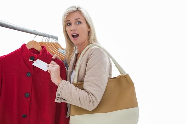 Bonita rubia sorprendida por el precio de la chaqueta