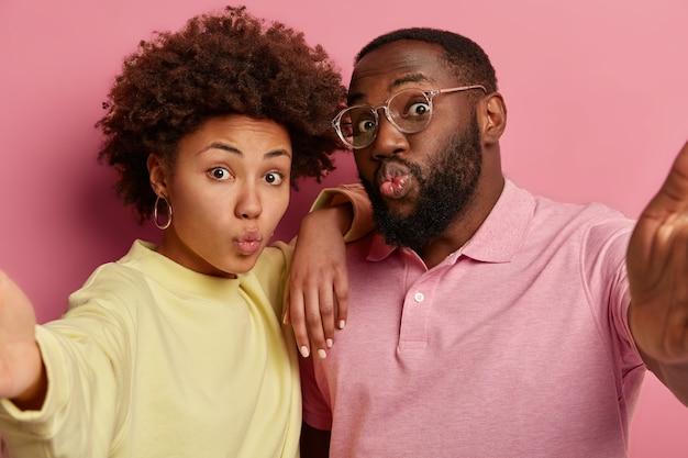 Bonita selfie. primer plano de una pareja de piel oscura que toma una foto con un dispositivo irreconocible, mantiene los labios redondeados, hace muecas a la cámara