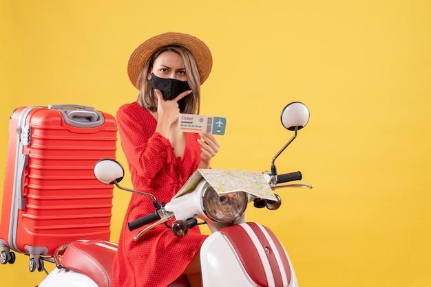 Bonita señorita con máscara negra en ciclomotor sosteniendo el boleto
