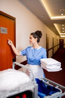Bonita sirvienta en uniforme sosteniendo una pila de toallas limpias mientras golpea la puerta de madera por la mañana
