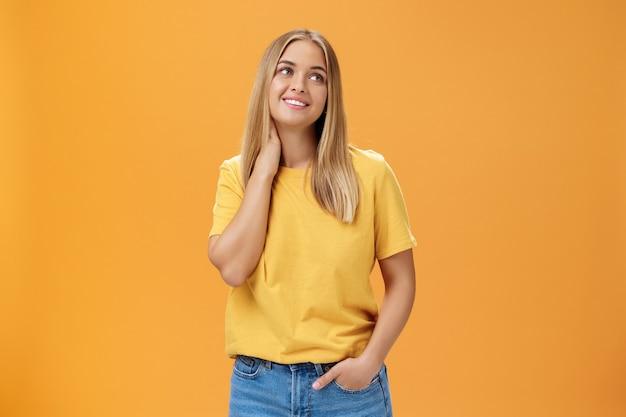 Bonita y tierna mujer independiente europea linda en camiseta amarilla suspirando tocando el cuello y mirando soñadora en la esquina superior derecha con una sonrisa agradable, posando sobre fondo naranja.