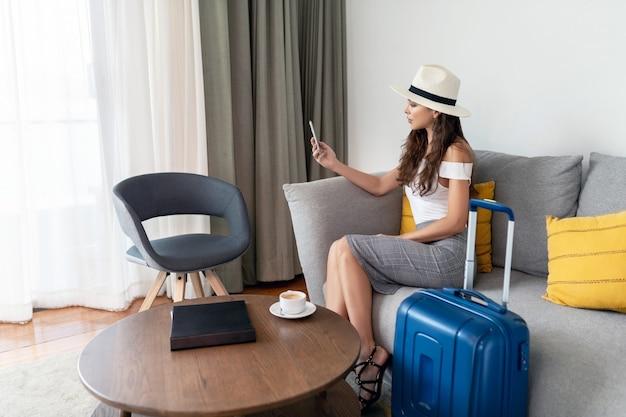 Bonita viajero-mujer tomando una selfie en el hotel. una mujer joven en un clásico sombrero y ropa feminista sentada en la silla y su equipaje cerca de ella, y ella se relaja después de volar.