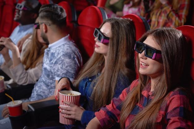Bonitas adolescentes disfrutando de la comedia en el cine