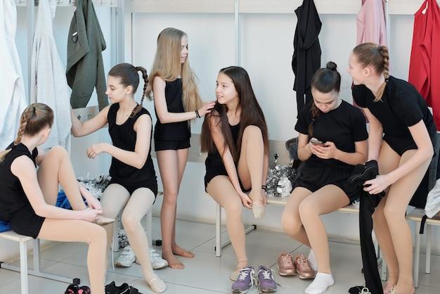 Bonitas gimnastas en monos negros sentados en bancos cambiándose de ropa y charlando mientras se cambian de zapatos