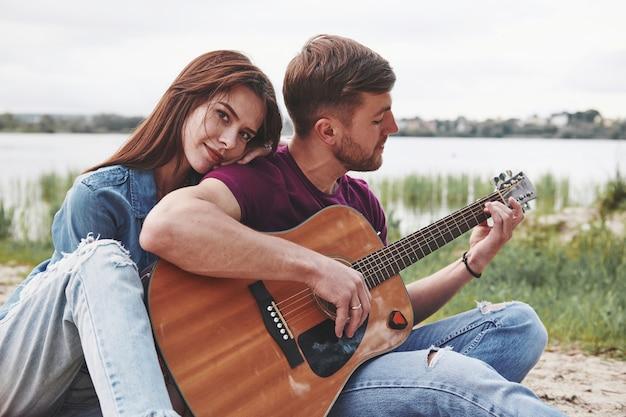 Bonitas habilidades. el hombre toca la guitarra para su novia en la playa en su picnic durante el día.