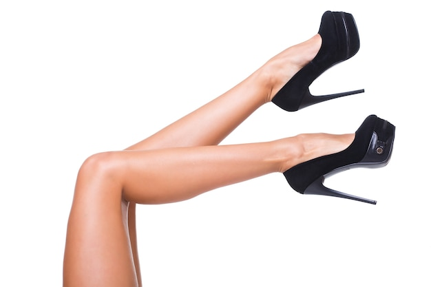 Bonitas piernas femeninas con tacones negros aislados sobre fondo blanco.