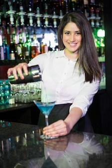 Bonito barman vertiendo una bebida de martini azul en el vaso en el bar