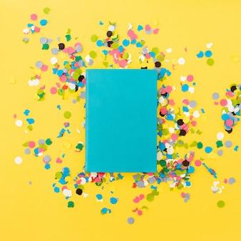 Bonito cuaderno para maqueta sobre fondo amarillo con confeti alrededor.