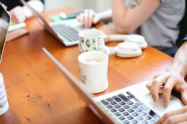 Bonito espacio de trabajo con computadoras portátiles y tazas de café.