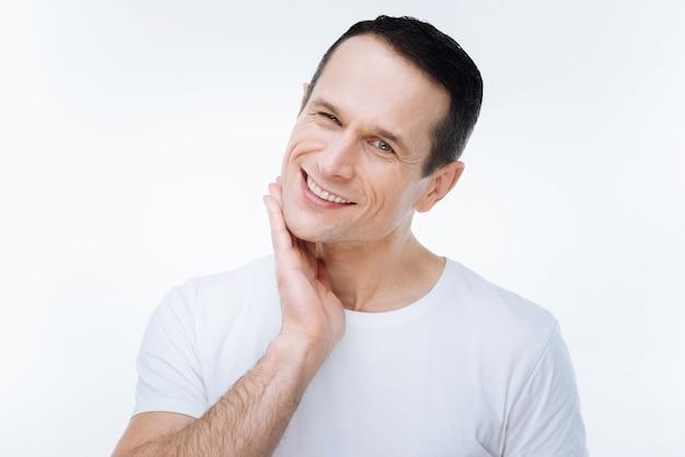 Bonito estilo. feliz hombre encantado girando la cabeza y tocando su barbilla mientras te mira